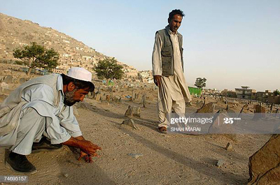 kabul afghanistan afghan men play with marbles at a muslim cemetery picture id74695157 400